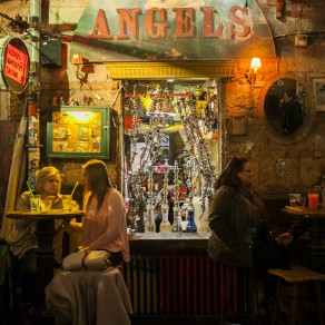 people drink at tables in front of the hookah station at szimpla kert ruin pub in budapest