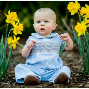a one year old sits among the daffodils