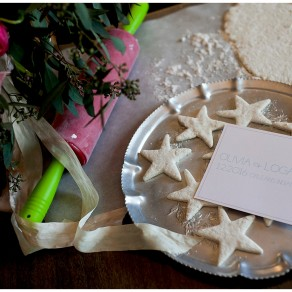 a save the date card next to star shaped biscuits and vintage rolling pin