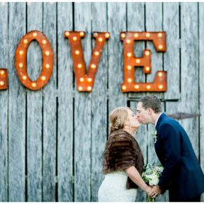 groom and bride in vintage fur in front of love marquee at drakewood farms